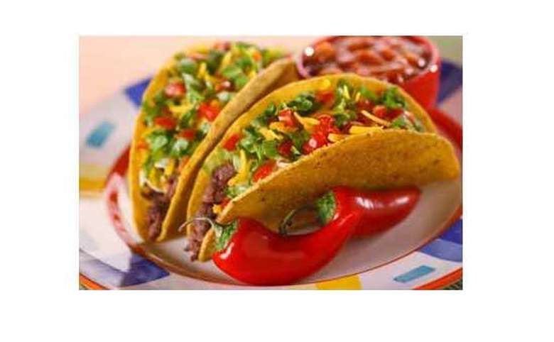 two beef tacos in corn tortillas on a multi-colored plate, with a side of beans in a bright red bowl, and two, whole, bright red chili peppers next to the tacos