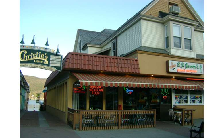 Another exterior view from the street. There is a red awning over an outdoor dining area at the entrance of the rstaurant.