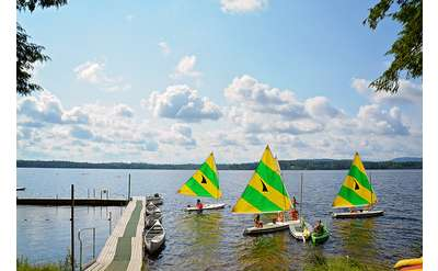 three yellow and green sailboats on the water