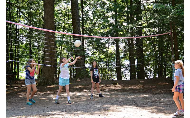 girls playing outdoor volleyball at camp
