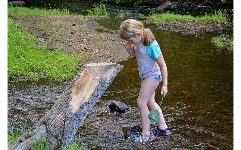 little girl playing by a creek