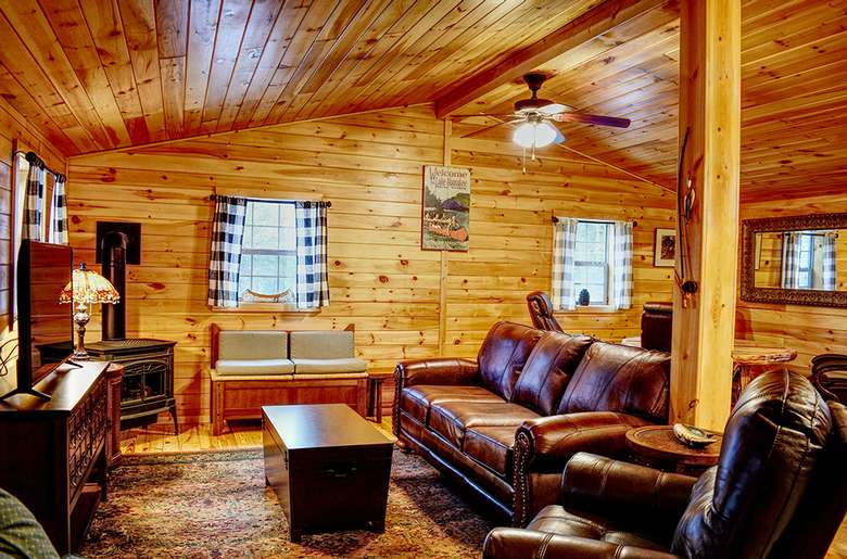 a rustic living room with leather sofa and chair, fireplace, and tv