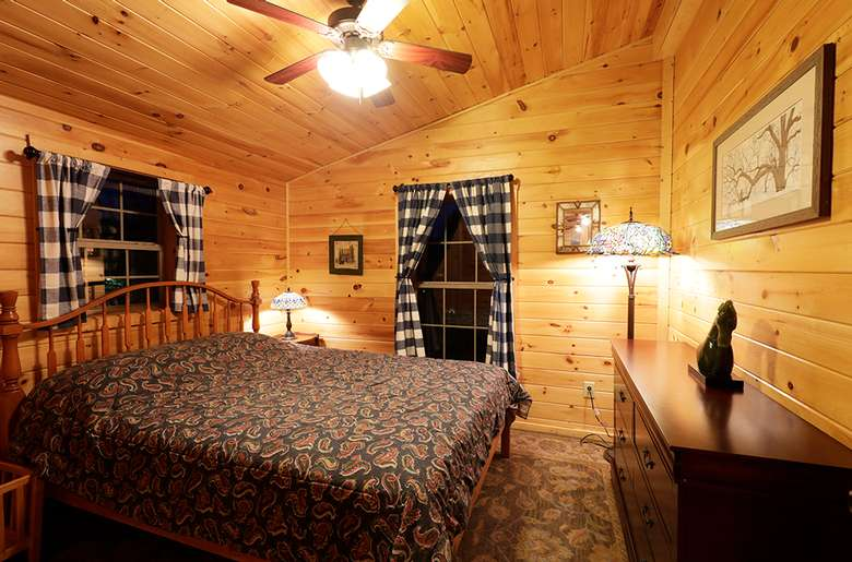 a master bedroom with a large bed and dresser