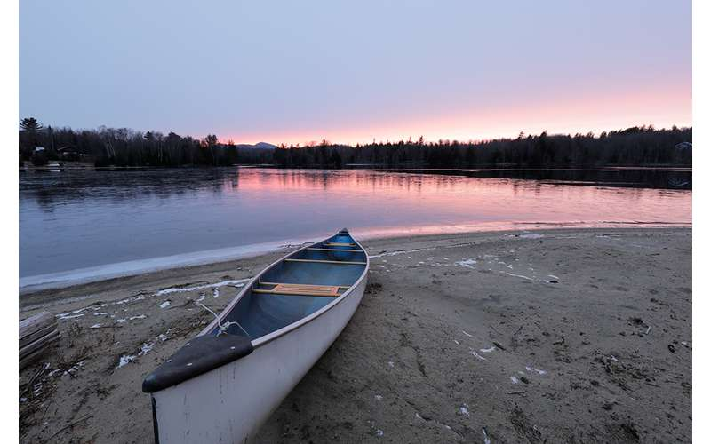 a sandy shoreline with a canoe