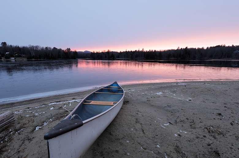 a sandy shoreline with a canoe