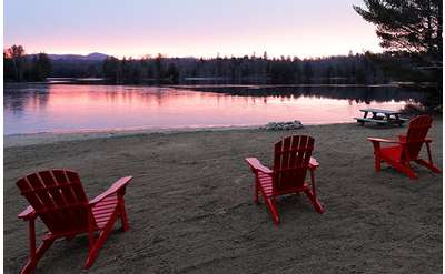 rows of red adirondack chairs on beach