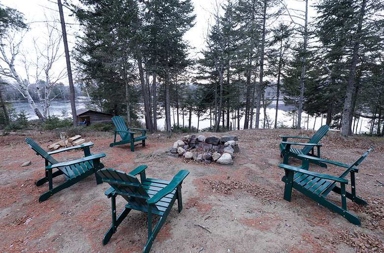 an outdoor fire pit surrounded by green adirondack chairs
