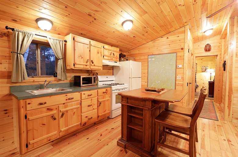 a rustic kitchen with wooden walls and cabinets, and an island with chairs