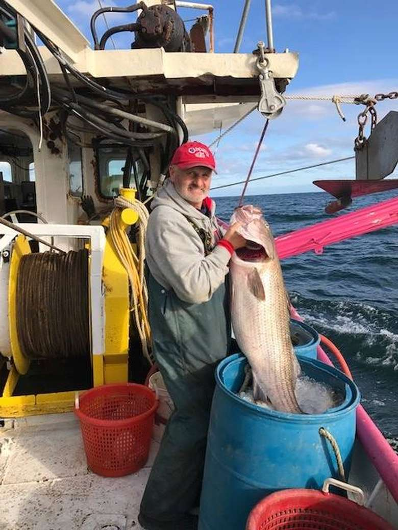man on a boat with a large fish in a bucket