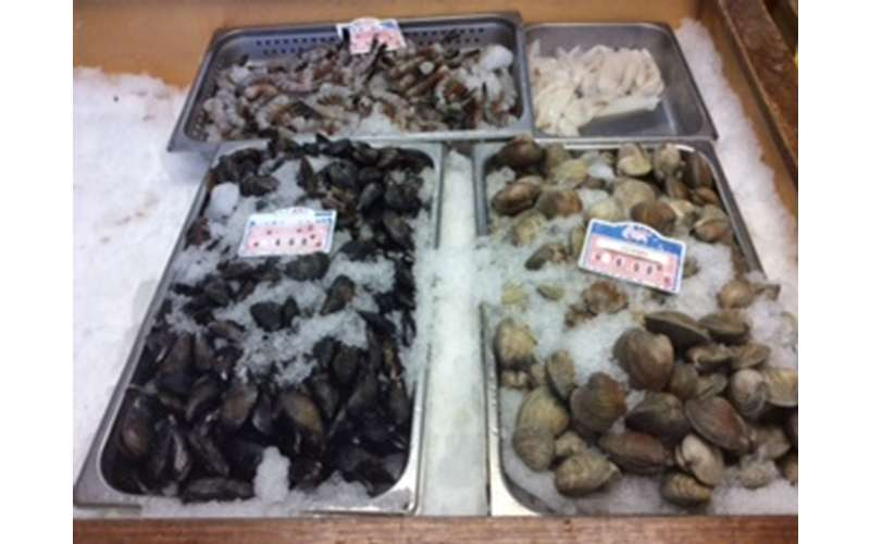 four bins filled with clams and other seafood