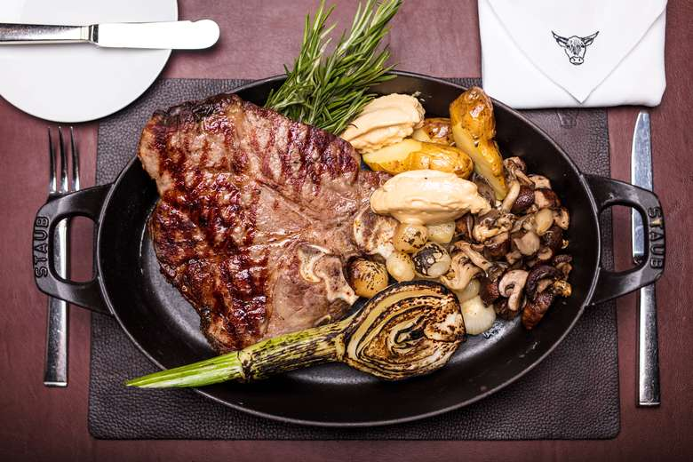 a plate of cooked steak and vegetables