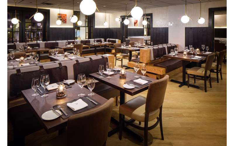 a large restaurant dining room with tables and overhanging lights