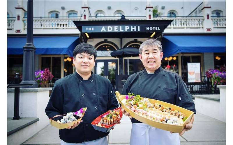 two men holding plates of sushi