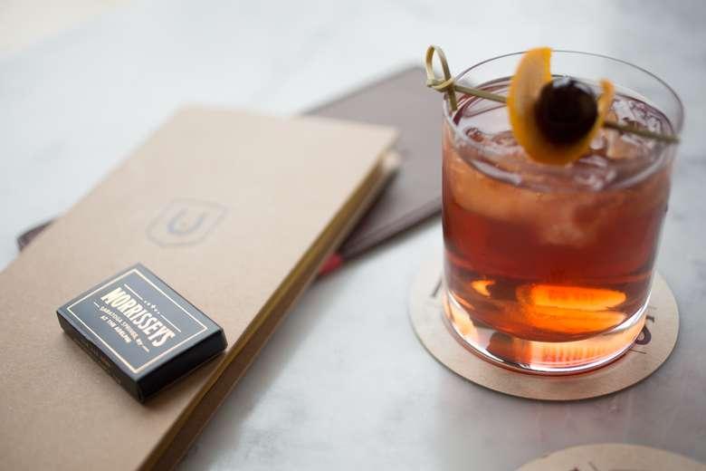 a cocktail next to a menu