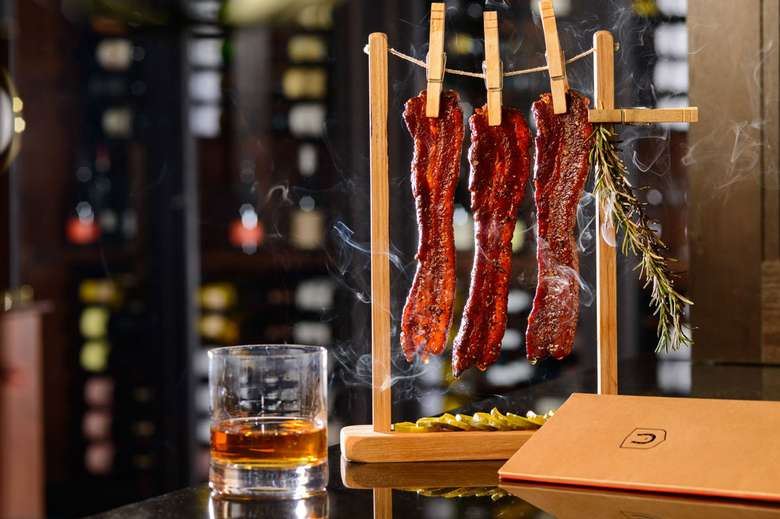 bacon hanging by clothespins next to a drink