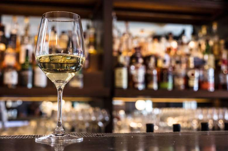 a glass of white wine on a bar