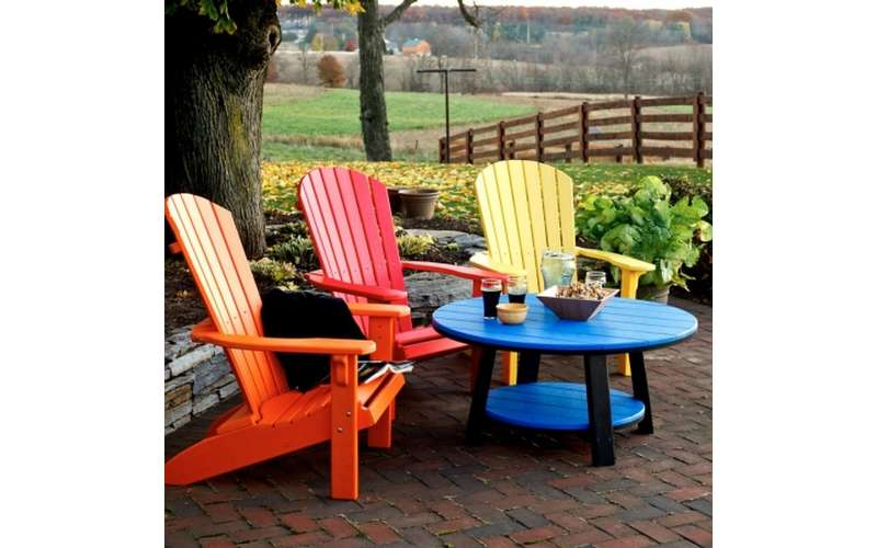 orange, red, and yellow colored Adirondack chairs around a blue table