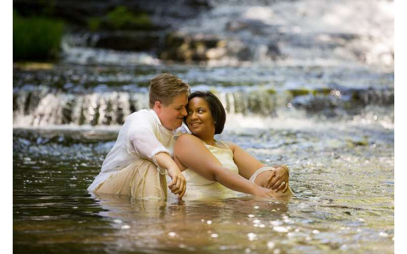 engagement shoot of man and woman sitting together in waterfall
