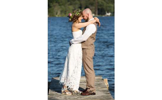 a bride and groom embracing near the waterfront on a dock