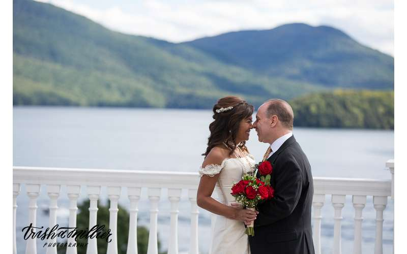 bride and groom about to kiss near lake