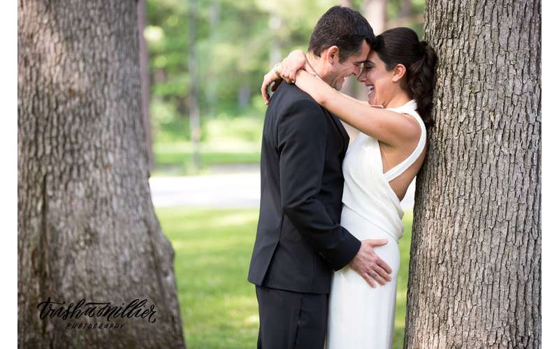 a bride and groom embracing near a tree