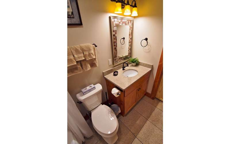a bathroom with a toilet next to the sink and cabinet