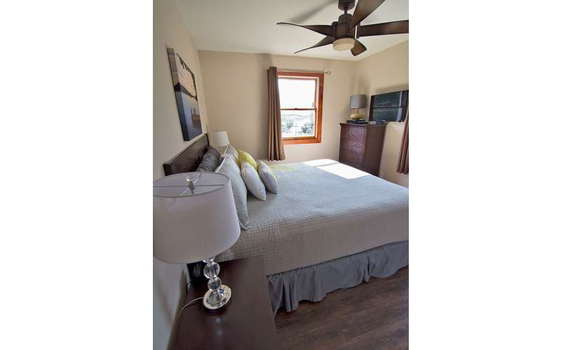 side view of a bed with a ceiling fan above