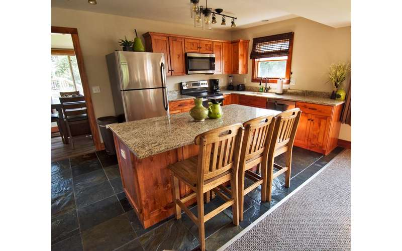 kitchen with fridge, wooden cabinets, and wooden island with granite countertop