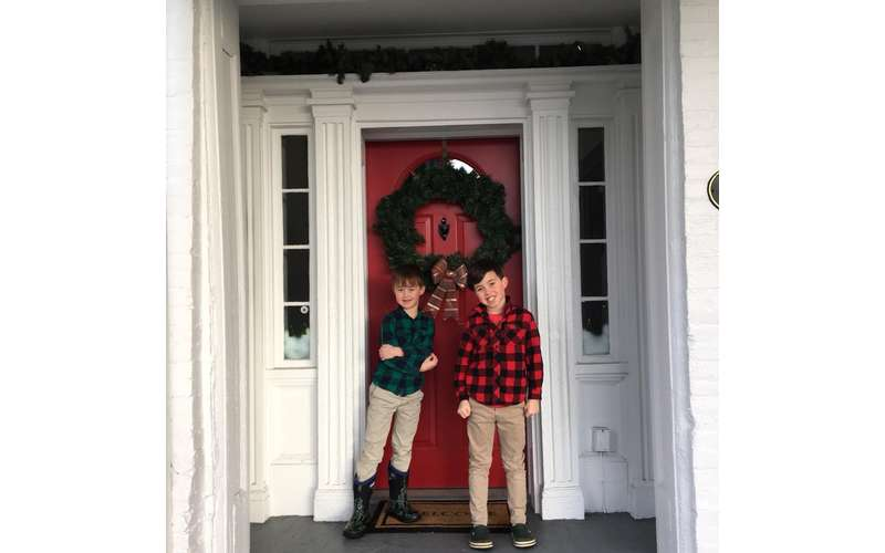 boys posing in front of a door with a wreath