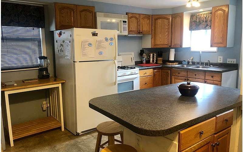 a kitchen with breakfast bar, fridge, oven, and more amenities