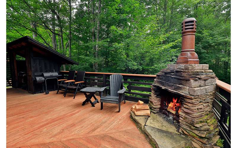 fireplace on a wooden patio deck near chairs and a grill