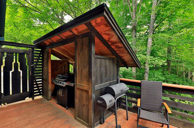 shed on a wooden deck with a grill inside