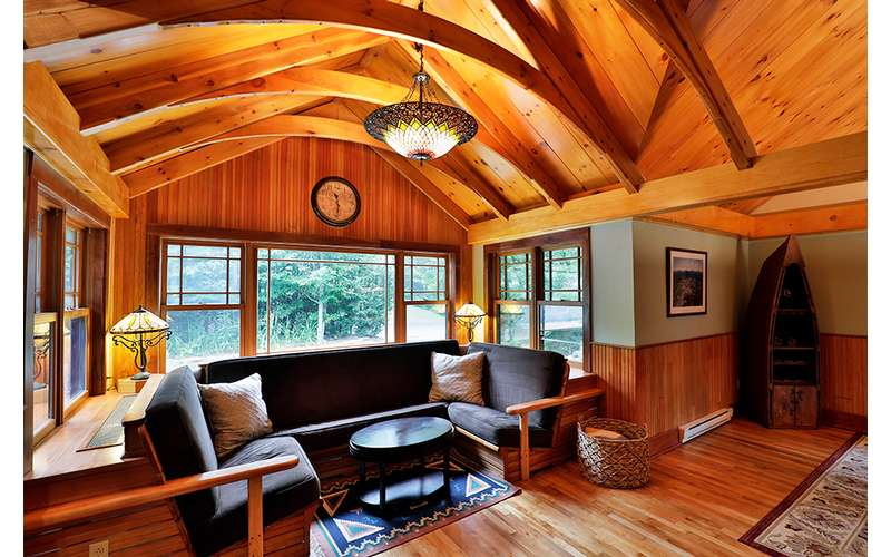 large living room with wooden walls and a big window in the back