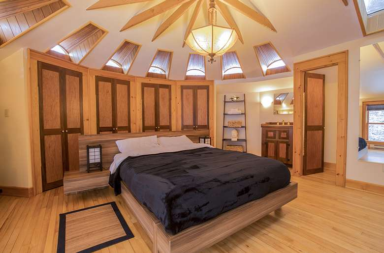 a well lit master bedroom with a large bed and shelves