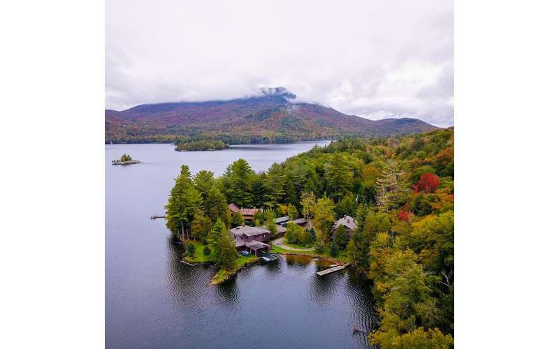 an aerial view of rustic lodges in the woods on the waterfront