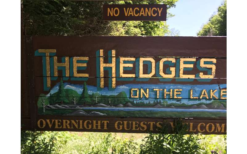 a sign for the hedges on the lake resort