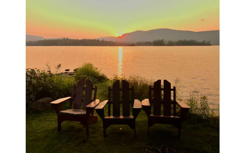 three Adirondack chairs with a sunset in the background
