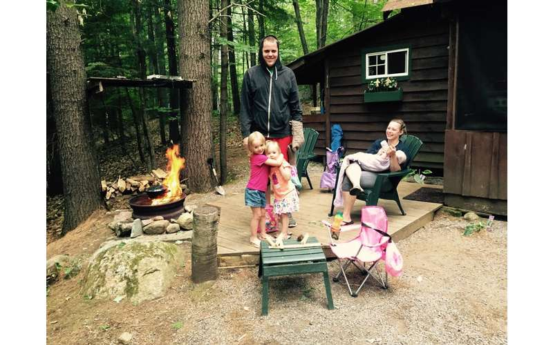 family on a small wooden patio near a fireplace and cottage