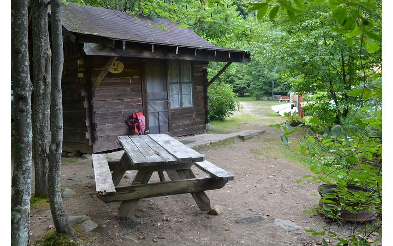 picnic table outside a small wooden cabin