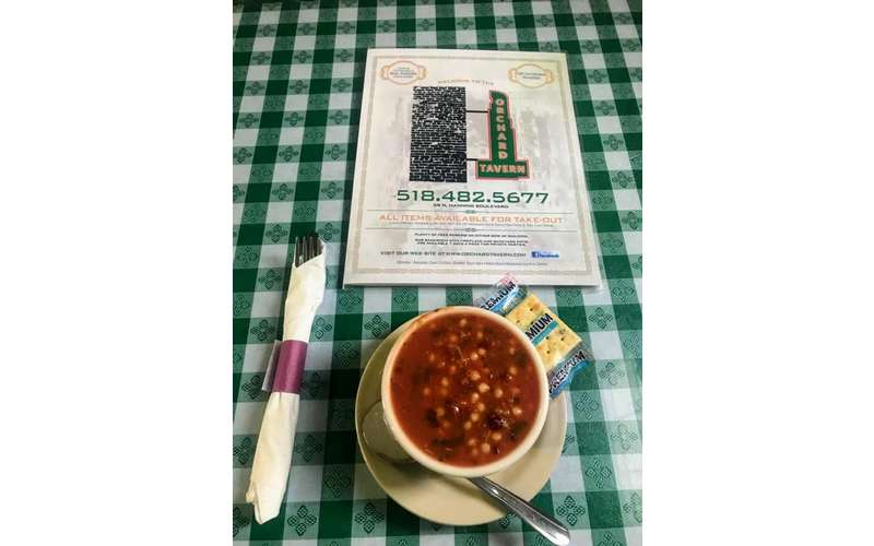 cup of soup on table with menu