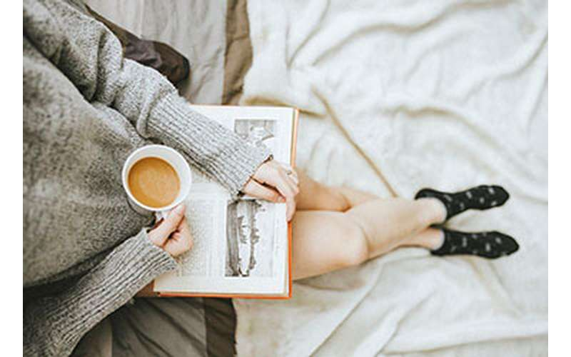 woman sitting with a book and coffee