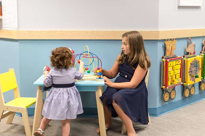 two girls playing with some games in a dental office