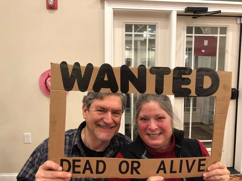 couple holding up Wanted Dead or Alive sign