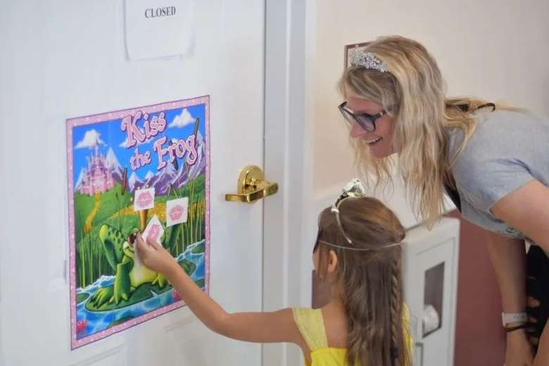 girl playing pin the lips on a frog