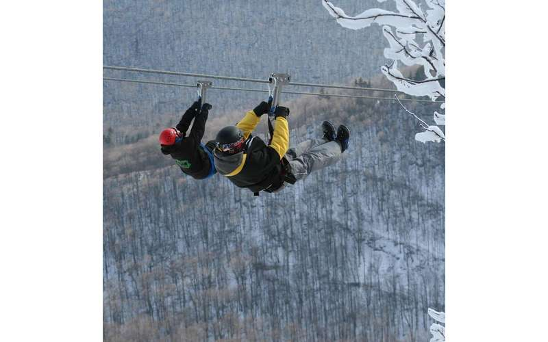 two people ziplining in winter