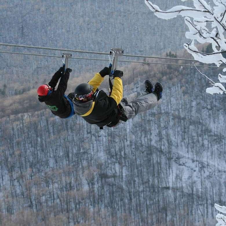 two people ziplining in winter