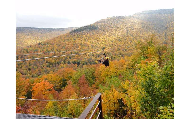 man ziplining while surrounded by beautiful fall foliage