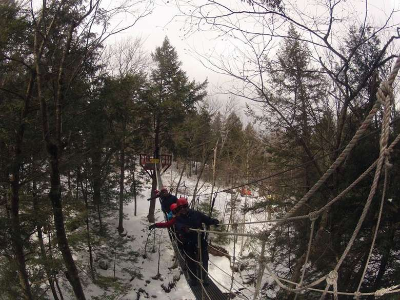 people on a ropes course bridge in winter