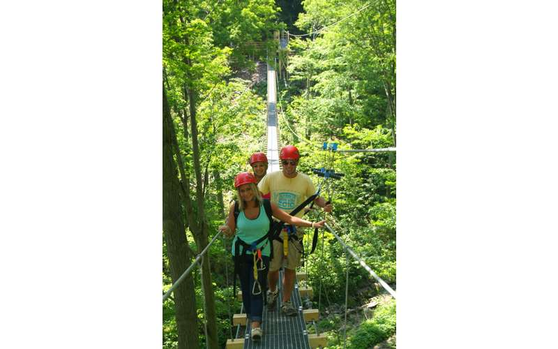 three people walking on a suspended bridge in the woods