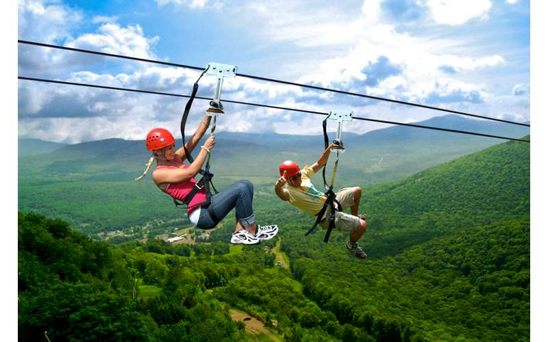 two people ziplining over a valley